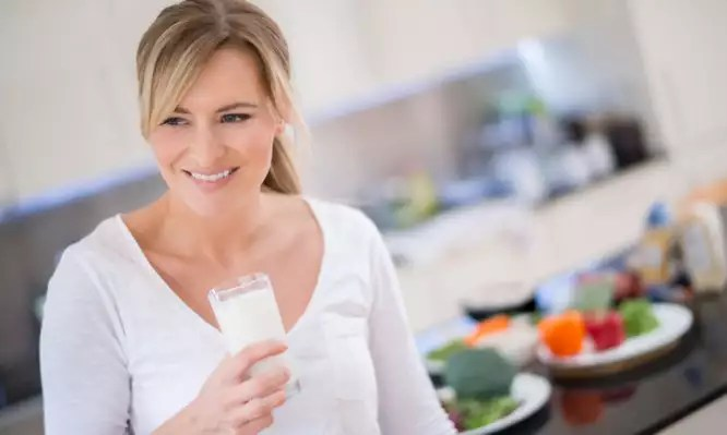 Woman holding a glass of milk and looking happy