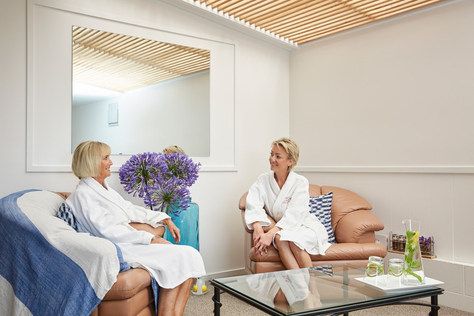 Two ladies relaxing, sitting in robes in our relaxation room