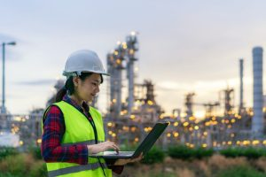 woman petrochemical engineer working at night with notebook Inside oil and gas refinery plant