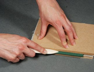 Using-Bonefolder-to-Crease-Cover-Material