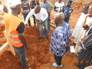 Le ministre d'Etat Simon Comporé suivant les explications de l'exécution des travaux sur le chantier de la cité CNSS