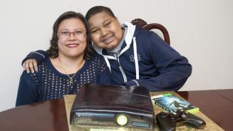 Christina Blunt smiles with her son Xavier Blunt after the nonprofit Icing Smiles worked with Crofton bakers Cakes 2-A-T o deliver a lifelike Xbox cake to him the day before his 13th birthday. Xavier recently received a liver transplant.