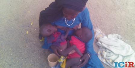 A hungry woman breastfeeds her twins