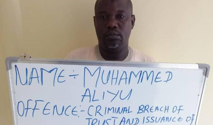Aliyu at the court premises displaying a board stating his offence. Photo Credit: EFCC