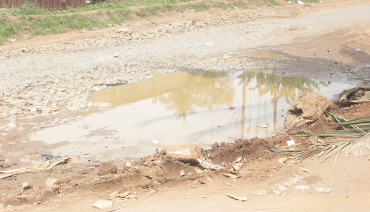 A failed section of the road with mud water logged in the middle. Photo by Patrick Egwu