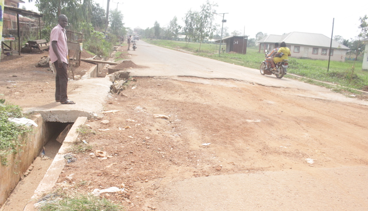 A man stands at an uncompleted section of the road. Photo by Patrick Egwu