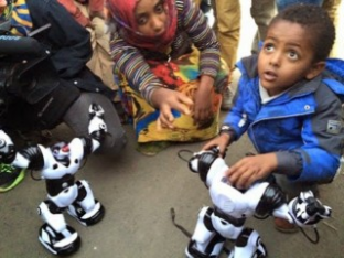 Young Ethiopian with robot whose AI software was created in his country.