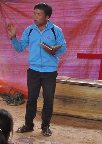 A preacher gives comfort to mourners during a believer's funeral service in Laos where believers are often prevented from holding funerals at all.