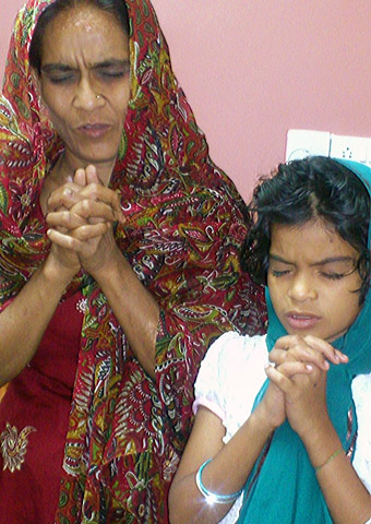 Vani and her daughter pray together after her recent release from prison.