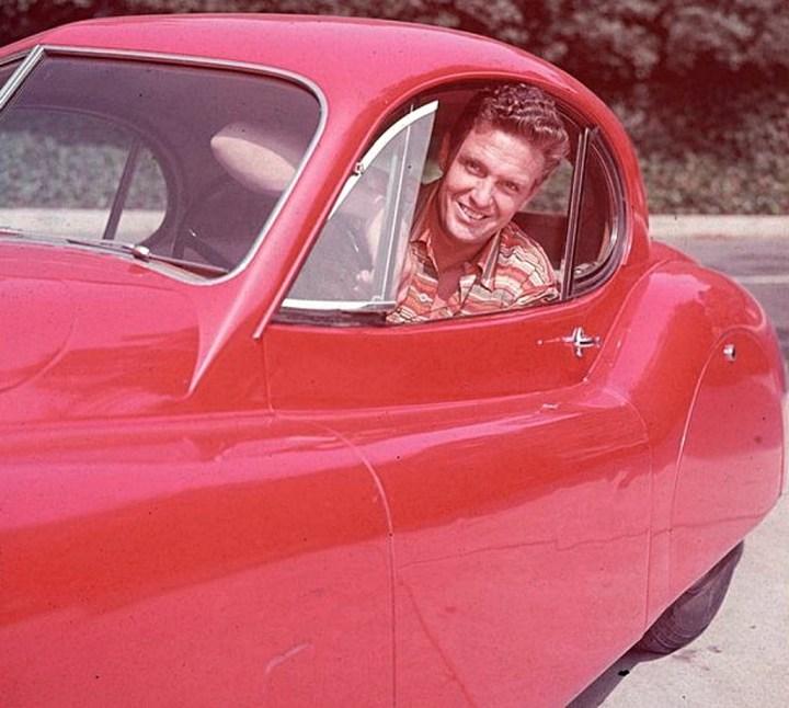 El actor Robert Stack sonríe desde su Jaguar XK120 fixed-head coupe hacia 1955 |Hulton Archive:Getty Images