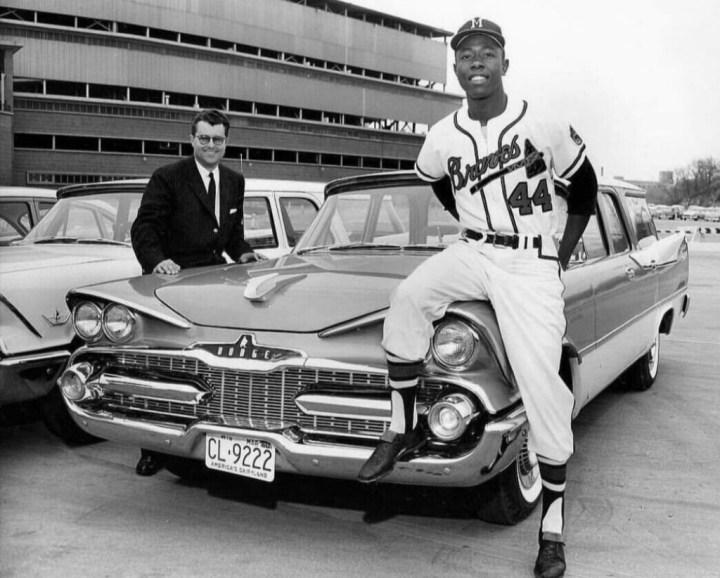El jugador de baseball Hank Aaron posa junto a un Dodge Station Wagon de 1959