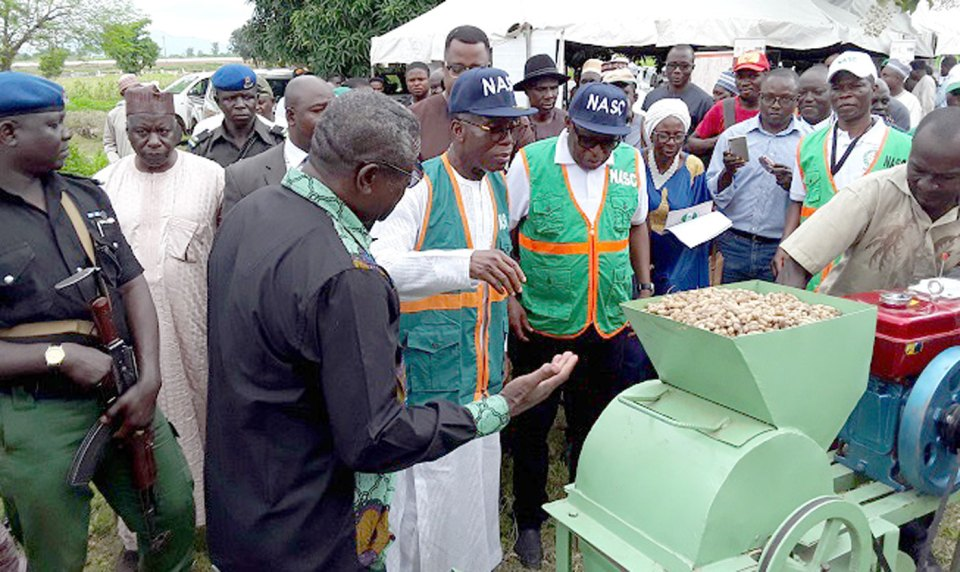 Dr Vabi explaining the working of motorized groundnut thresher to Chief Audu Innocent Ogbeh, Federal Minister of Agriculture and Rural Development, Nigeria, and Dr Philip Ojo, Director General of NASC.