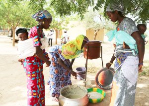 A group of women in Sirakele Village, Sikasso region of Mali serve porridge as part of Africa RISING'S endeavor for nutrition sensitive agriculture. The project is working with women having children aged 4 - 8 months in southern Mali. Photo: Jonathan Odhong/IITA