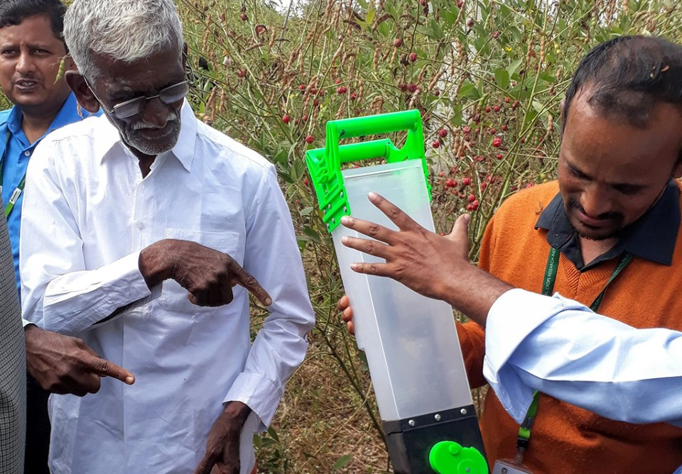 Farmer Bhimrao Mulgi and Mr Raghavendra, Scientific Officer, ICRISAT, demonstrate the seed dibbler, a lightweight handheld tool to quickly and easily sow seeds. It can be adjusted to release one or more seeds at a time. Photo: Rajani Kumar, ICRISAT