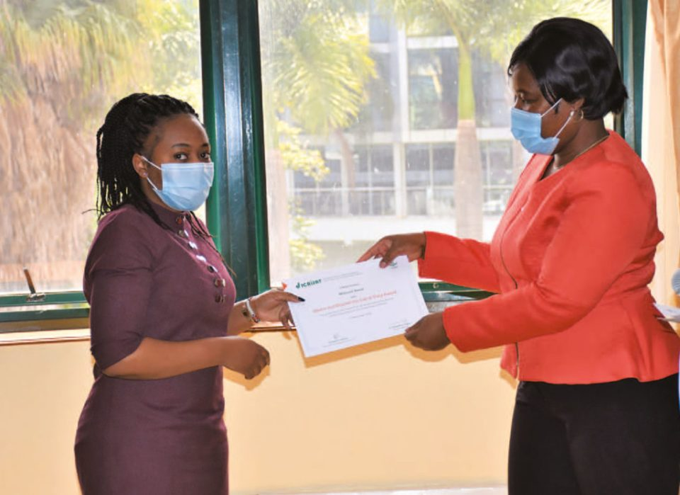 Dr Rebbie Harawa, Research Program Director, ESA, hands Ms Millicent Avosa a certificate in honor of her work during the pandemic. Photo: ICRISAT, Nairobi