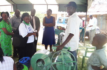 Ms Philigona is briefed on how a locally-made groundnut sheller works. Photos: D Otwani, ICRISAT