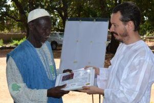 ICRISAT scientist P.C.S. Traore officially transmits the set of certificates to the Sukumba Village Chief, Mr. Yakuba Berthe for the award ceremony to collaborating farmers.