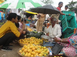 Ms Archer (L), interacting with vegetable vendors.