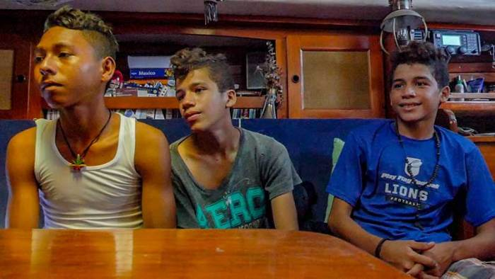 The boys watch a sailing video in Oleada's cabin.