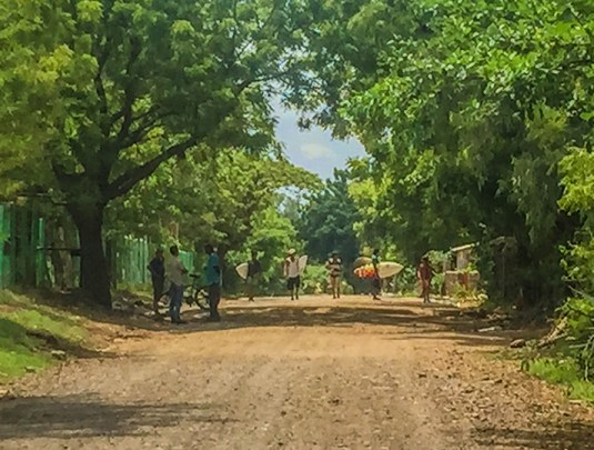 This low-resolution photo captures the laidback feeling around Aserradores: local kids walk the dirt road to the surf break, unworried and unhurried by traffic. Men stand chatting in the shade with their trusted transport, the bicycle.