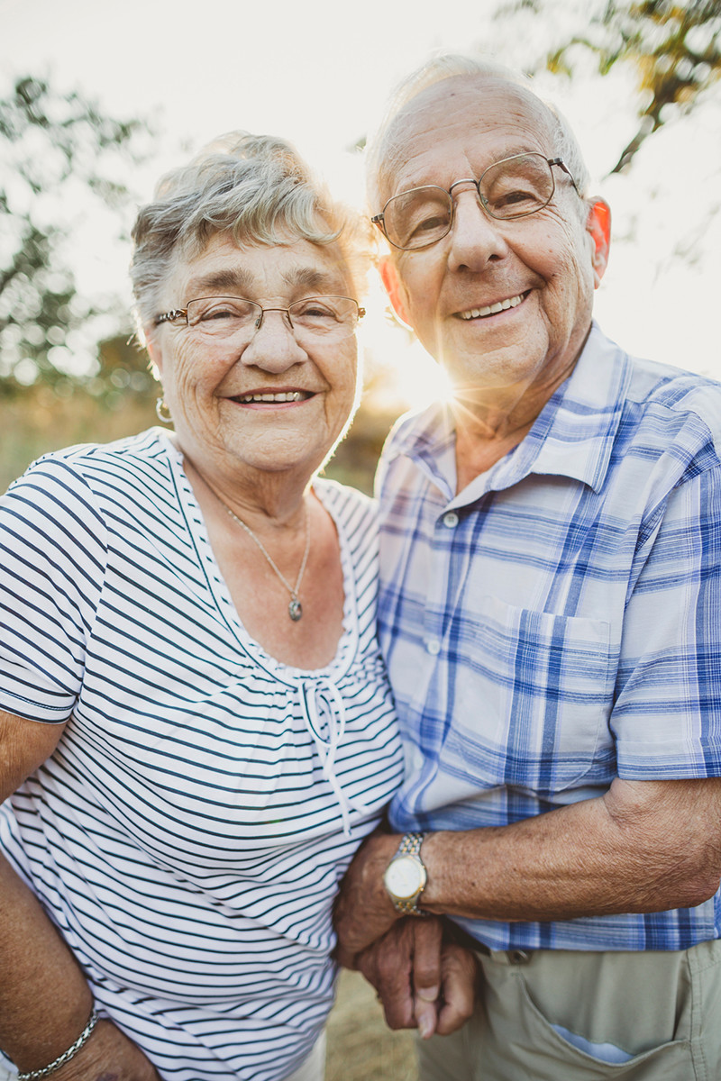senior couple holding hands and smiling
