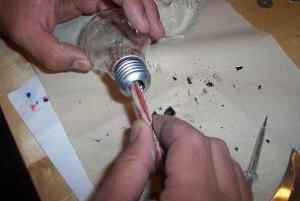 togliere i filamenti interni della lampadina con una pinzetta