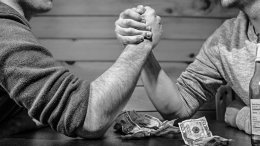 two guys arm wrestling at a bar in black and white