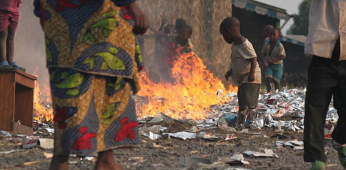 Plastic and other waste burning in the open while children look on in a refugee camp in the DRC.