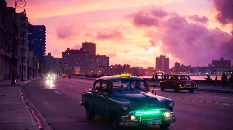 How to travel to Cuba as an American - an old fashioned car on the Malecon in Cuba