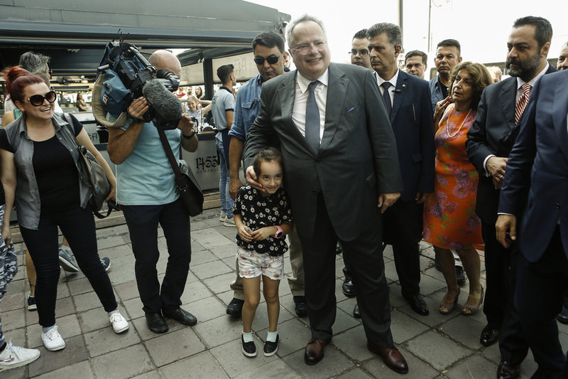 Ο Ν. Κοτζιάς ποζάρει αγκαλιά με ένα παιδάκι στη Σμύρνη -Φωτογραφία: ΑΠΕ-ΜΠΕ/ΓΙΑΝΝΗΣ ΚΟΛΕΣΙΔΗΣ