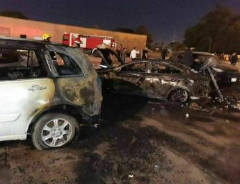 ifmat - Charred cars are seen after a rocket strike on the Green Zone in central Baghdad
