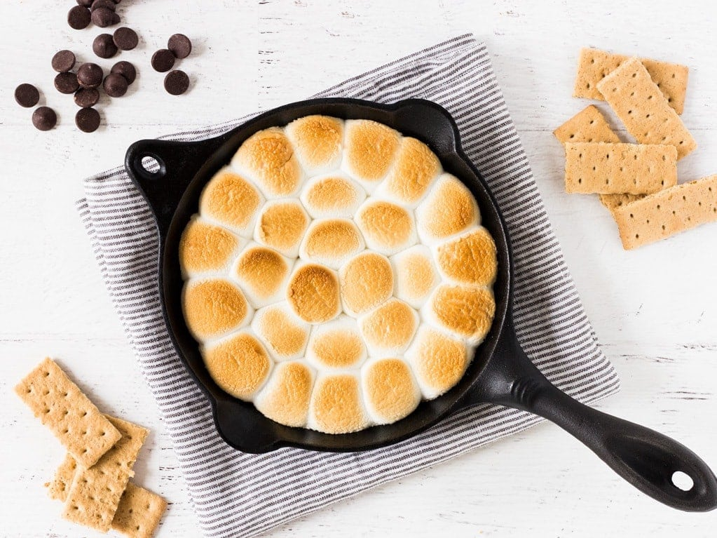 How to make smores dip with chocolate chips, marshmallows and graham crackers.   www.ifyougiveablondeakitchen.com