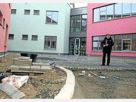 Grünes Klassenzimmer: Schulleiter Erhard Zammert im Lichthof zwischen den drei Gebäuden, wo später naturnaher Unterricht unter freiem Himmel möglich sein wird. Foto: Stier