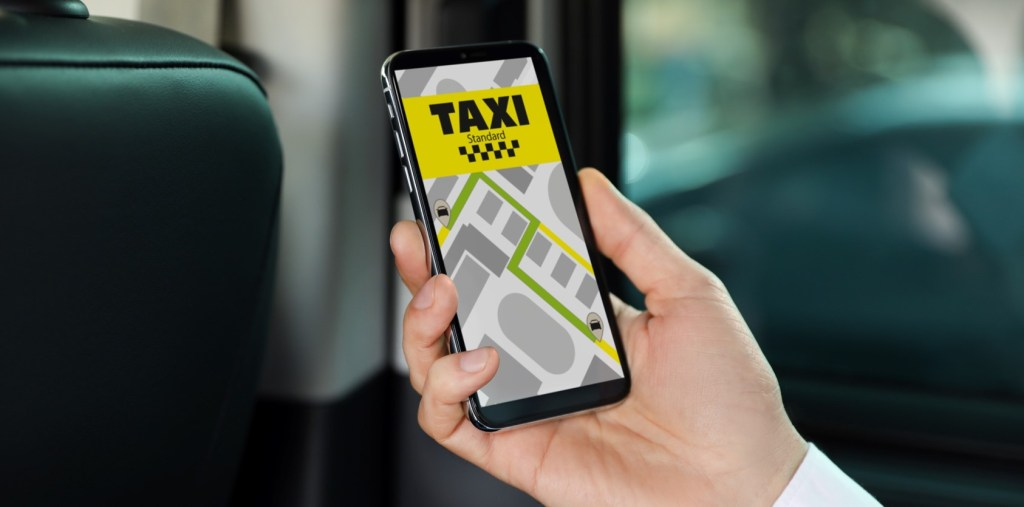 A photo of a hand holding a phone with a ride-hailing taxi app open