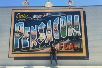 Standing in front of the Pensacola sign