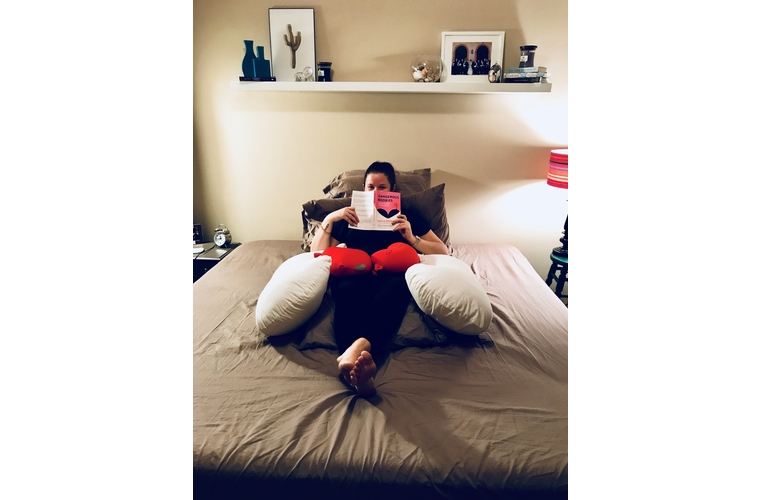 Mackenzie peeking over book on bed in mastectomy pillow fort