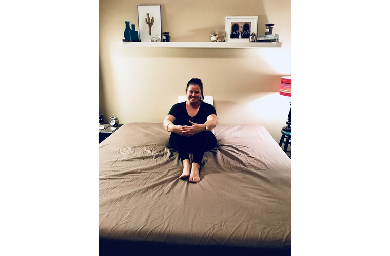 Mackenzie sitting on bed with wedge pillow after mastectomy
