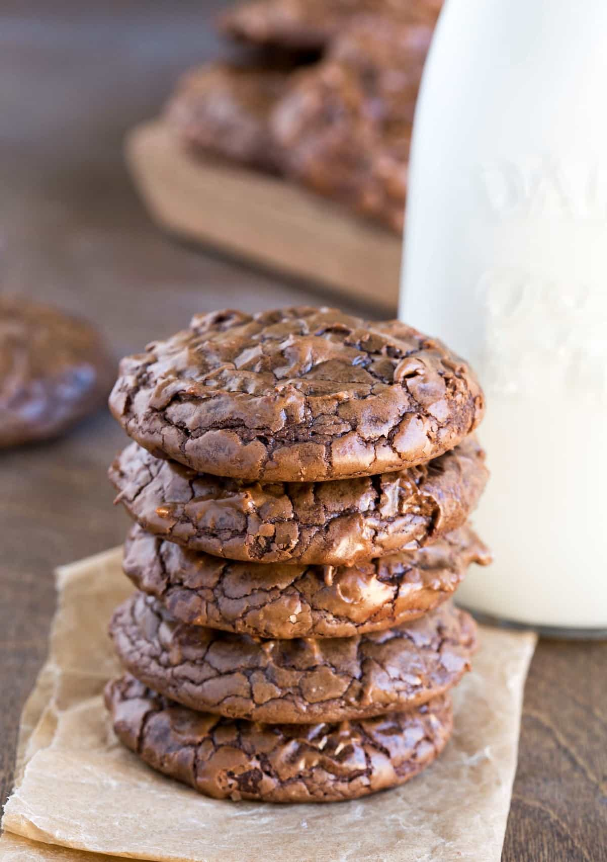 Stack of brownie cookies on a piece of brown parchment paper next to a milk bottle