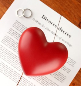 red heart with torn Divorce decree document, on wooden backgroun
