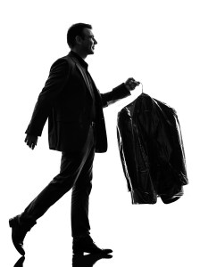 one caucasian business man holding dry clean clothes in silhouet