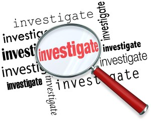 Magnfiying glass on the word investigate to illustrate detective