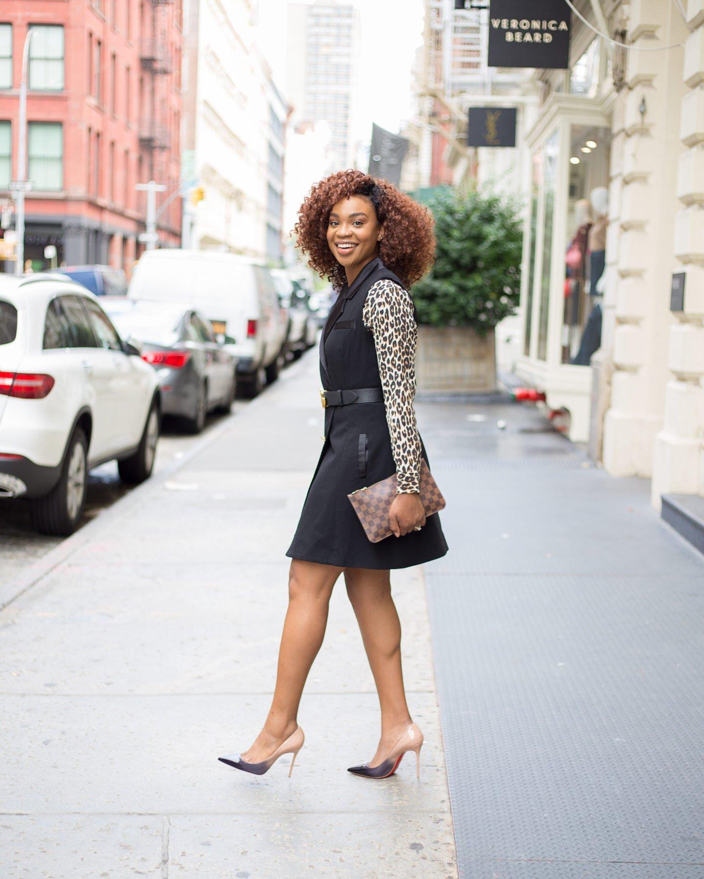 Lifestyle blogger Ijeoma Kola wears Equipment leopard print shirt, Slate & Willow sleeveless blazer dress, Gucci belt, Louis Vuitton zip pouch, and Louboutin decollete 554