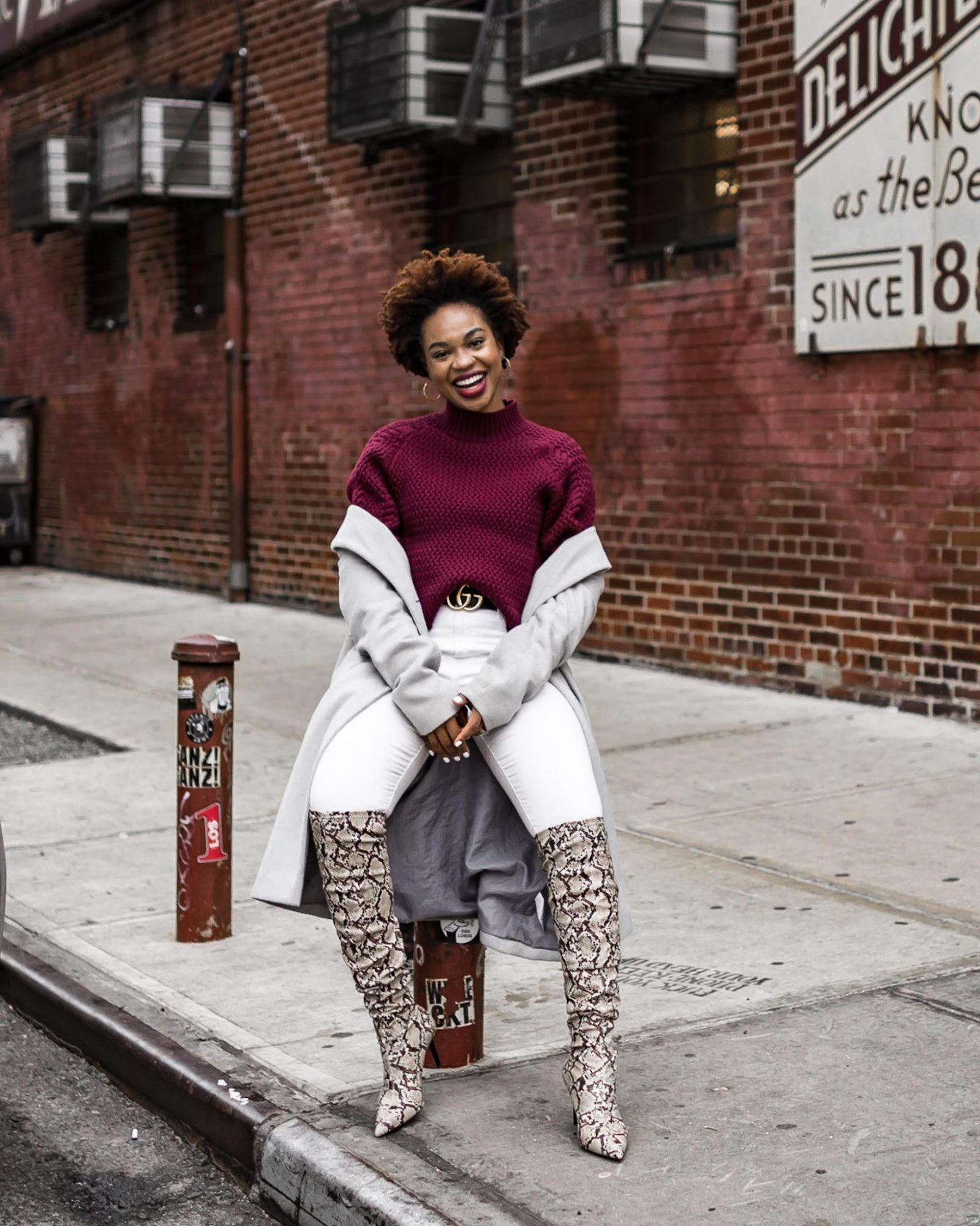 Lifestyle blogger Ijeoma Kola wears snakeskin otk boots, white jeans, chunky sweater, and a gucci belt