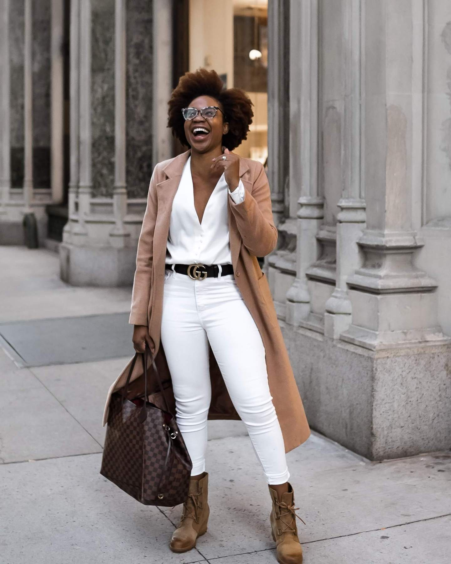 Lifestyle blogger Ijeoma Kola wears white and camel winter outfit with Louis Vuitton Neverfull tote bag