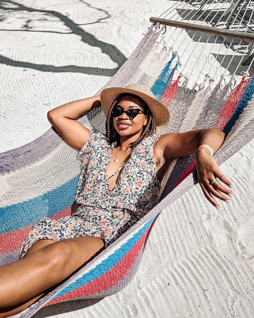 Ijeoma Kola wears Veronica Beard brynlee dress and reverse cat eye sunglasses while lying in a hammock