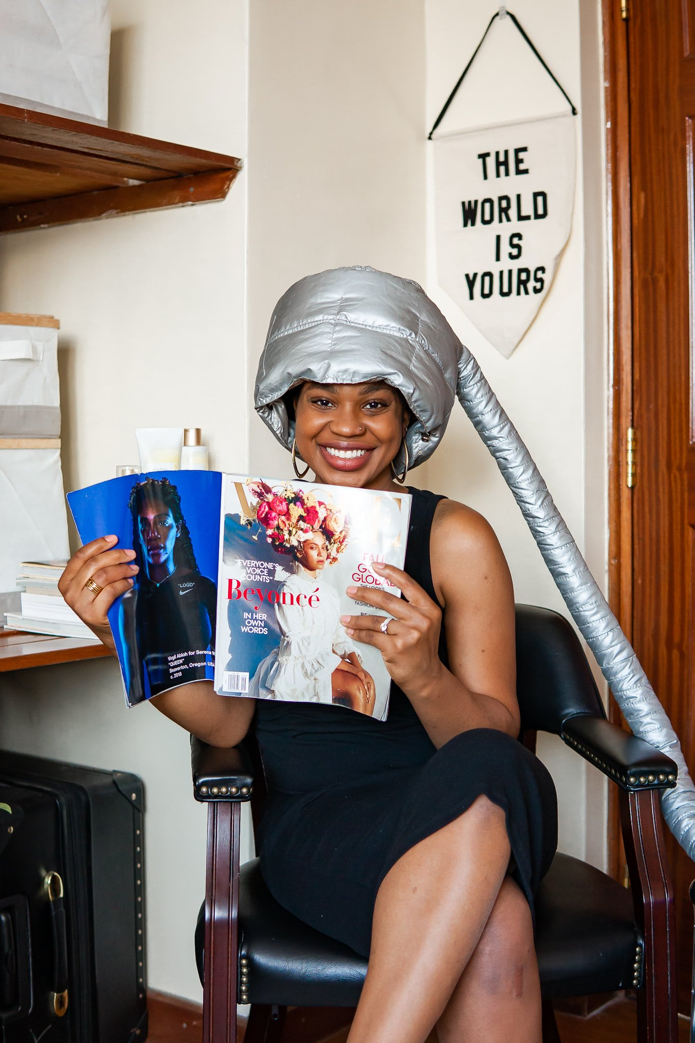 Ijeoma Kola reading magazine with hair dryer and 'The World Is Yours' wall art