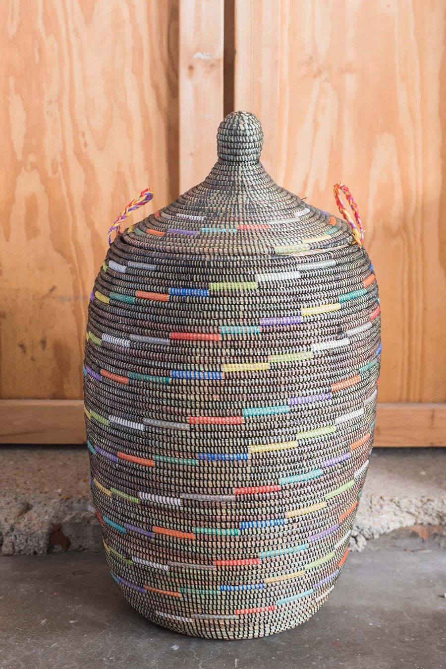 Black woven basket with multicolored accents