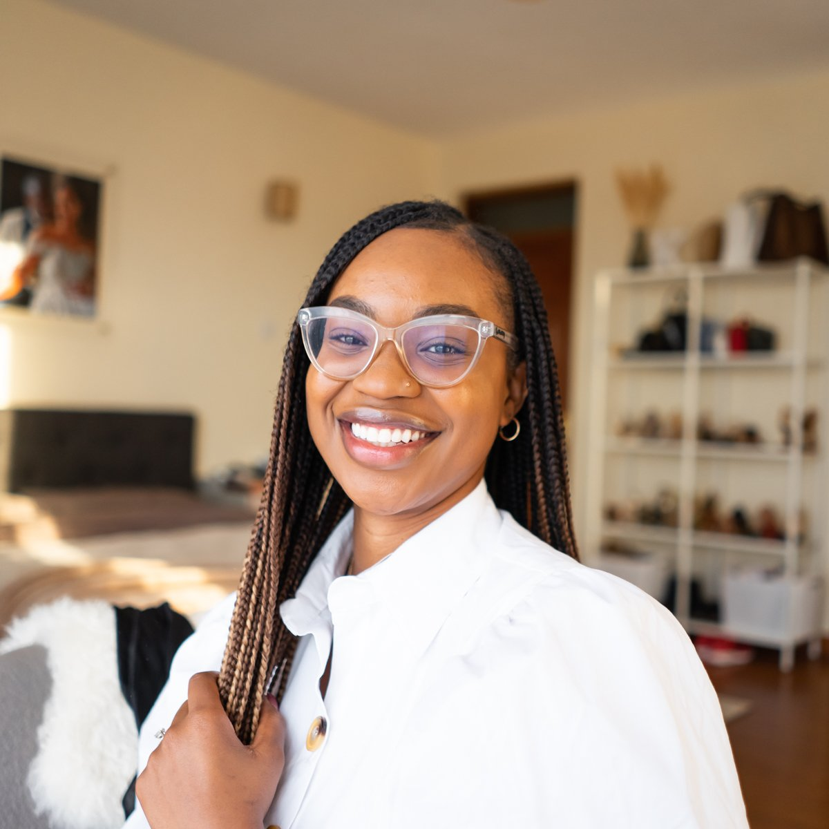 Ijeoma Kola smiling in clear glasses and knotless braids