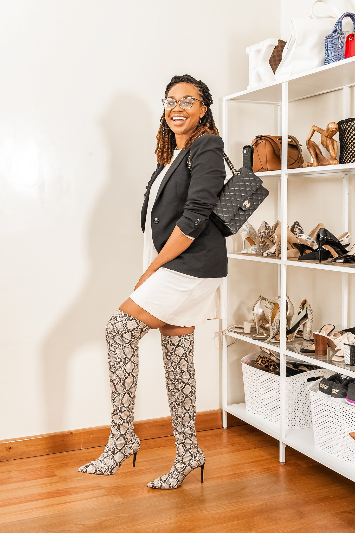 Ijeoma Kola in black fall blazer with white shirt dress, thigh high snake skin boots and black Chanel bag.