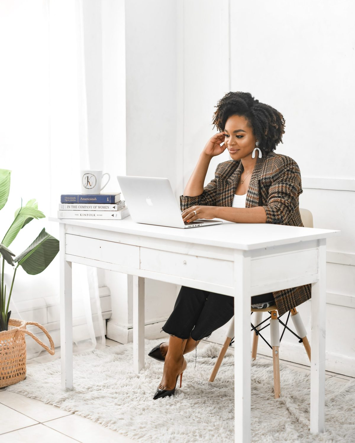Blogger sitting at desk in blazer and louboutin heels